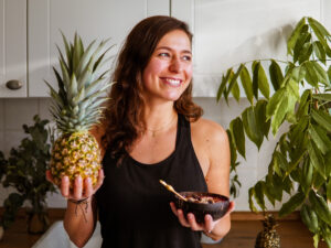 Frau hält Ananas in der rechten und Smoothie Bowl in der linken Hand