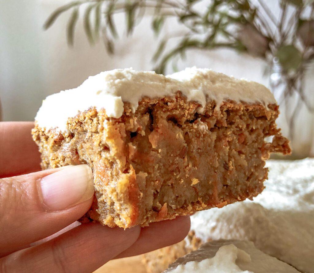 ein Stück Carrot Cake in einer Hand gehalten