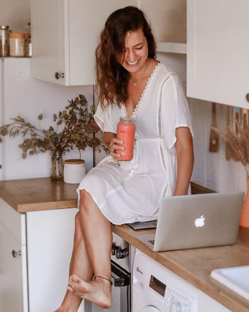 junge Frau sitzt in der Küche auf dem Herd mit Smoothie und Laptop