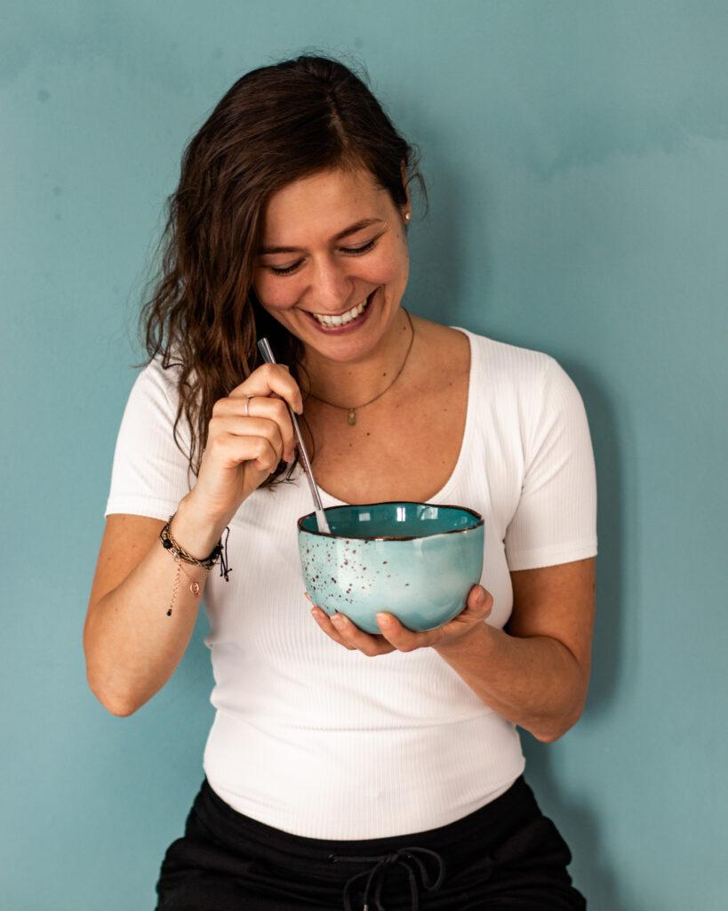lachende Frau mit blauer Schüssel in der Hand