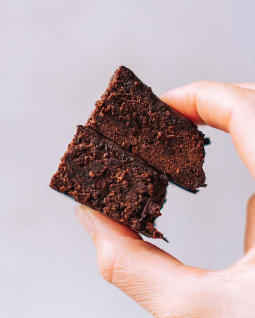 2 Schokoladenbrownies zwischen Daumen und Zeigefinger gehalten